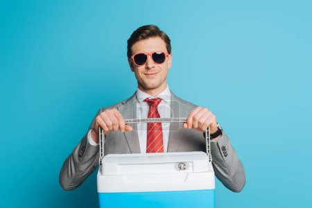 Photo for Happy businessman in sunglasses holding portable fridge on blue background - Royalty Free Image