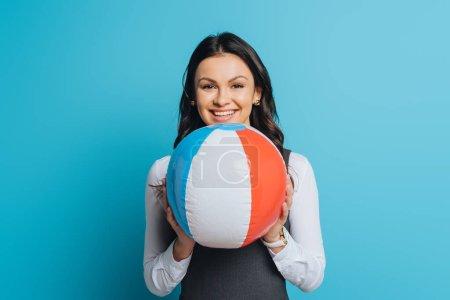 Photo pour Femme d'affaires heureuse tenant ballon gonflable tout en souriant à la caméra sur fond bleu - image libre de droit
