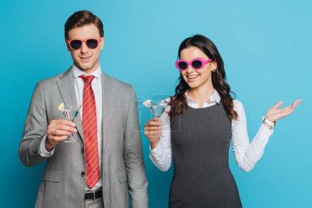 Photo pour Homme d'affaires joyeux et femme d'affaires dans des lunettes de soleil célébrant des vacances avec des lunettes de cocktail sur fond bleu - image libre de droit