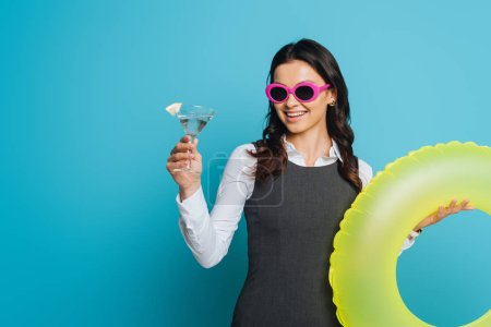 Photo for Cheerful businesswoman in sunglasses holding glass of cocktail and swim ring on blue background - Royalty Free Image