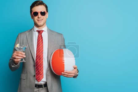 Photo for Happy businessman in sunglasses holding glass of cocktail and inflatable ball on blue background - Royalty Free Image