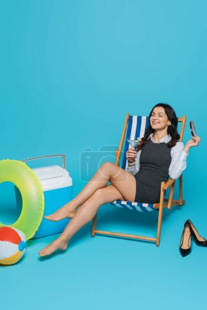 Photo for Happy businesswoman sitting with closed eyes in deck chair with glass of cocktail near portable fridge, inflatable ring and ball on blue background - Royalty Free Image