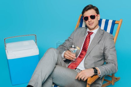Photo for Happy businessman in sunglasses sitting in deck chair with glass of cocktail near portable fridge on blue background - Royalty Free Image
