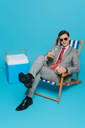 Photo for Smiling businessman in sunglasses sitting in deck chair with glass of cocktail near portable fridge on blue background - Royalty Free Image
