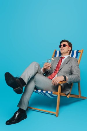 Photo for Happy businessman in sunglasses sitting in deck chair with glass of cocktail on blue background - Royalty Free Image