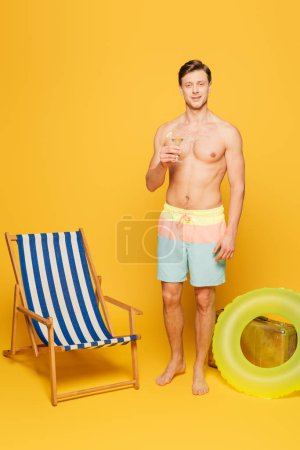 Photo for Shirtless man in shorts holding glass of cocktail near deck chair, swim ring and vintage suitcase on yellow background - Royalty Free Image