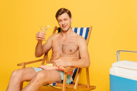 Photo for Happy shirtless man sitting in deck chair near portable fridge and holding glass of cocktail on yellow background - Royalty Free Image