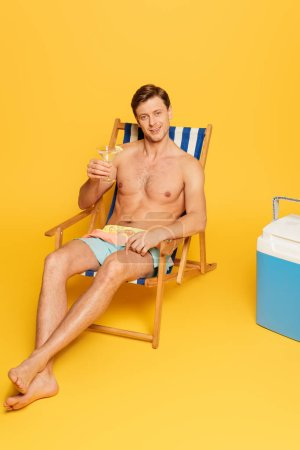 Photo for Handsome shirtless man sitting in deck chair near portable fridge and holding glass of cocktail on yellow background - Royalty Free Image