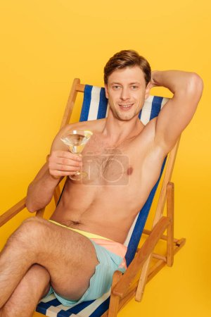 Photo for Handsome shirtless man sitting in deck chair and holding glass of cocktail isolated on yellow - Royalty Free Image
