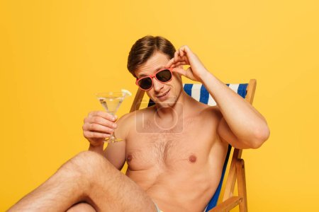 Photo for Handsome man touching sunglasses while sitting in deck chair, looking at camera and holding glass of cocktail isolated on yellow - Royalty Free Image