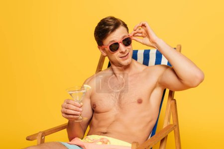 Photo for Handsome man touching sunglasses while sitting in deck chair, looking away and holding glass of cocktail isolated on yellow - Royalty Free Image
