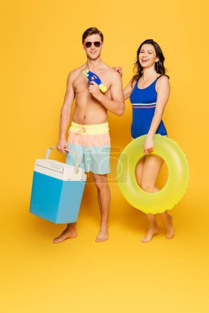 Photo for Handsome shirtless man holding portable fridge and sunglasses near smiling girlfriend with swim ring on yellow background - Royalty Free Image