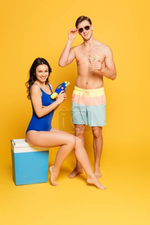 Photo for Cheerful woman sitting on portable fridge with water gun near shirtless man with glass of cocktailon yellow background - Royalty Free Image
