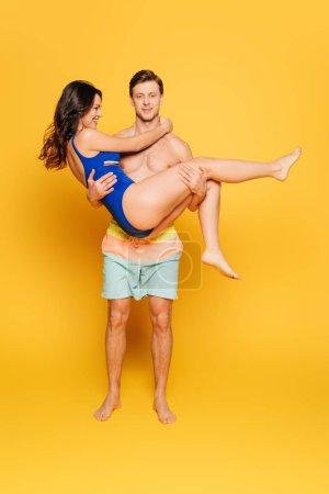 Photo pour Beau homme sans chemise tenant une amie heureuse en maillot de bain sur fond jaune - image libre de droit