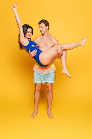 handsome shirtless man holding excited girlfriend in swimsuit on yellow background