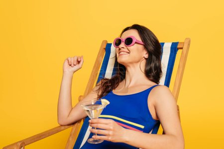 Photo for Happy woman in swimsuit and sunglasses resting in deck chair while holding glass of cocktail isolated on yellow - Royalty Free Image