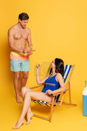 Photo for Handsome shirtless man proposing glass of cocktail to attractive woman sitting in deck chair on yellow background - Royalty Free Image