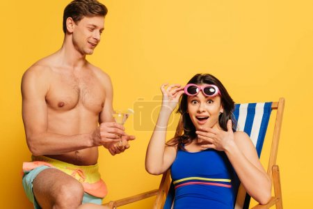 Photo for Handsome shirtless man proposing glass of cocktail to amazed woman touching sunglasses and looking at camera on yellow background - Royalty Free Image
