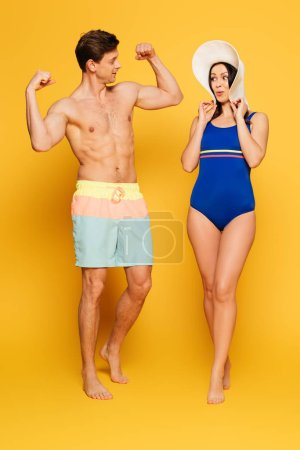 amazed woman in swimsuit looking at handsome shirtless man demonstrating biceps on yellow background