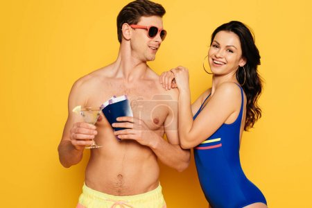 Photo for Happy woman in swimsuit leaning on shoulder of shirtless man holding glass of cocktail, passports and air tickets on yellow background - Royalty Free Image