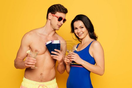 Photo for Happy couple with glasses of cocktail, passports and air tickets on yellow background - Royalty Free Image