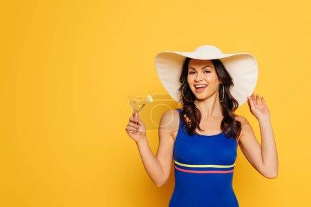 Photo pour Femme heureuse en maillot de bain touchant chapeau de soleil tout en tenant verre de cocktail isolé sur jaune - image libre de droit