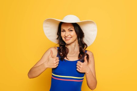 Photo for Cheerful woman in sun hat and swimsuit showing thumbs up isolated on yellow - Royalty Free Image