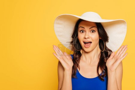 attractive, surprised woman in sun hat showing wow gesture isolated on yellow
