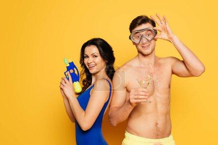 Photo pour Homme gai masque de plongée tenant verre de cocktail près femme heureuse avec pistolet à eau sur fond jaune - image libre de droit