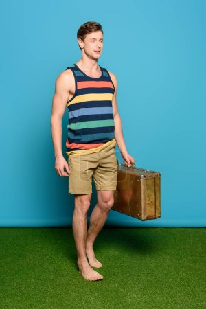 Photo for Handsome man in striped singlet and shorts holding vintage suitcase on blue background - Royalty Free Image