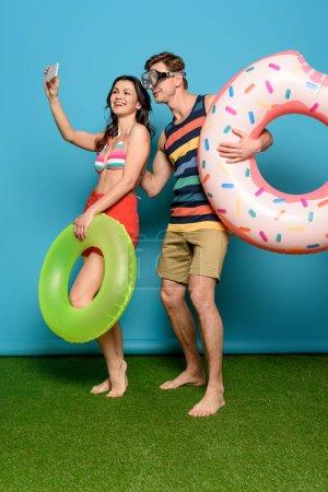 Photo pour Couple gai avec anneaux gonflables prenant selfie sur smartphone sur fond bleu - image libre de droit