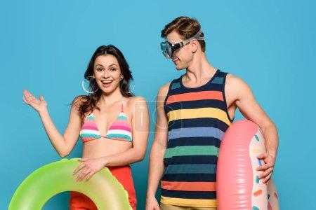 Photo pour Femme gaie debout avec bras ouvert et homme souriant dans le masque de plongée tenant anneaux gonflables sur fond bleu - image libre de droit