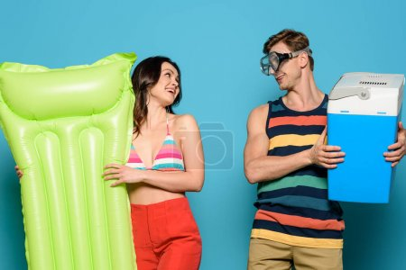 Photo for Man in diving mask holding portable fridge near cheerful woman with inflatable mattress on blue background - Royalty Free Image