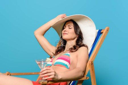Photo pour Attrayant, femme heureuse bronzer dans la chaise longue tout en tenant un verre de cocktail sur fond bleu - image libre de droit