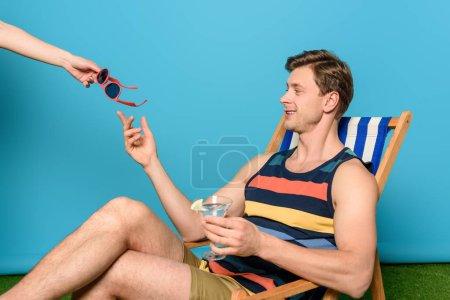 Photo pour Vue partielle de la femme donnant des lunettes de soleil à un homme souriant assis sur une chaise longue et tenant un verre de cocktail sur fond bleu - image libre de droit