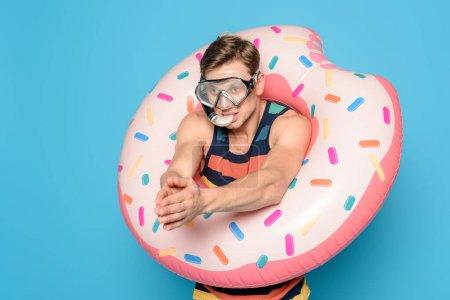 Photo pour Jeune homme en anneau de natation, masque de plongée et pipe imitant la plongée sur fond bleu - image libre de droit
