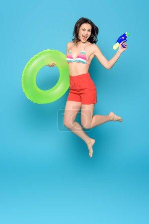 Photo pour Une joyeuse femme saute avec son anneau gonflable et son canon à eau sur fond bleu - image libre de droit