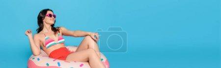 Photo pour Plan panoramique de la belle femme en maillot de bain de soleil assis sur l'anneau de bain isolé sur bleu - image libre de droit