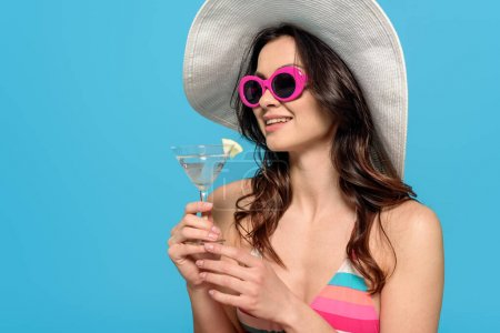 Photo for Happy stylish woman in sunglasses and sun hat holding glass of cocktail isolated on blue - Royalty Free Image