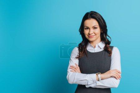Lächelnde Geschäftsfrau, die mit verschränkten Armen in die Kamera blickt