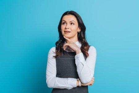 Photo pour Cher femme d'affaires regardant loin tout en touchant le menton sur fond bleu - image libre de droit
