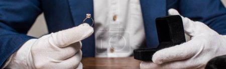Photo pour Vue recadrée de l'évaluateur de bijoux tenant la bague avec pierre précieuse et boîte sur la table isolée sur gris, vue panoramique - image libre de droit