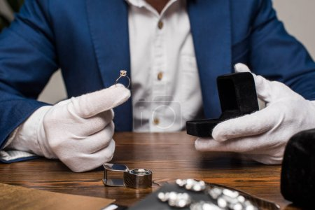 Photo pour Cropped view of jewelry appraiser holding ring with gemstone and box on table on grey background - image libre de droit