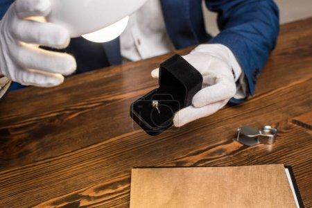 Photo pour Vue recadrée de l'évaluateur de bijoux tenant la bague avec pierre précieuse dans la boîte près de la lampe à la table isolée sur gris - image libre de droit