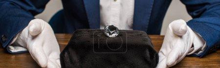 Photo pour Vue recadrée de l'évaluateur de bijoux en gants près de pierres précieuses sur une table en bois isolée sur fond gris, vue panoramique - image libre de droit