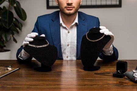 Photo pour Vue agrandie d'un évaluateur de bijoux tenant des colliers avec des colliers près de bijoux sur une table dans un atelier - image libre de droit
