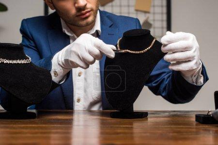 """Photo pour Vue agrandie de l """"évaluateur de bijoux en gants tenant des pinces près d'un collier sur un support de collier sur une table - image libre de droit"""