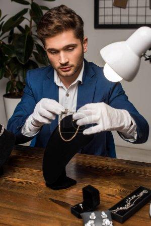 Photo pour Beau évaluateur de bijoux en gants tenant collier près du stand de collier et bijoux sur la table - image libre de droit