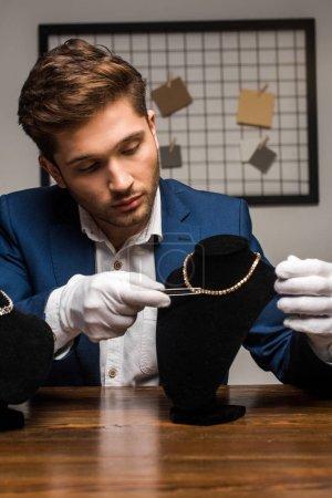 Photo pour Beau évaluateur de bijoux tenant une pince à épiler près du collier sur piédestal sur table en atelier - image libre de droit