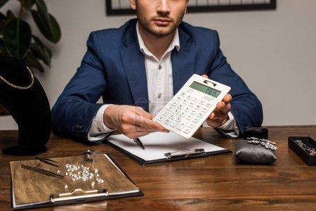 Photo pour Vue recadrée de l'évaluateur de bijoux montrant la calculatrice près du presse-papiers et des bijoux sur la table - image libre de droit